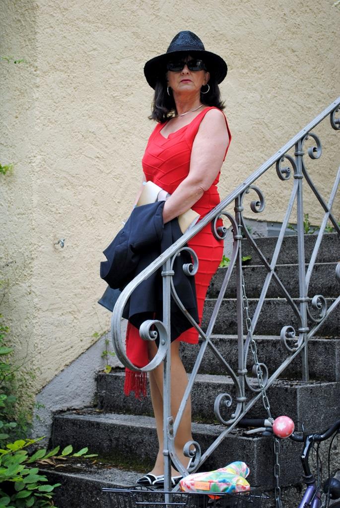 Rotes Etuikleid mit Hut und Tasche