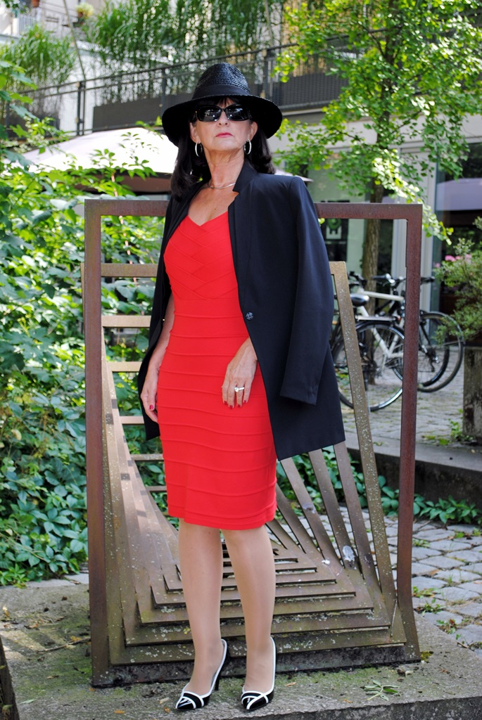 Rotes Etuikleid mit Hut und schwarzem Blazer