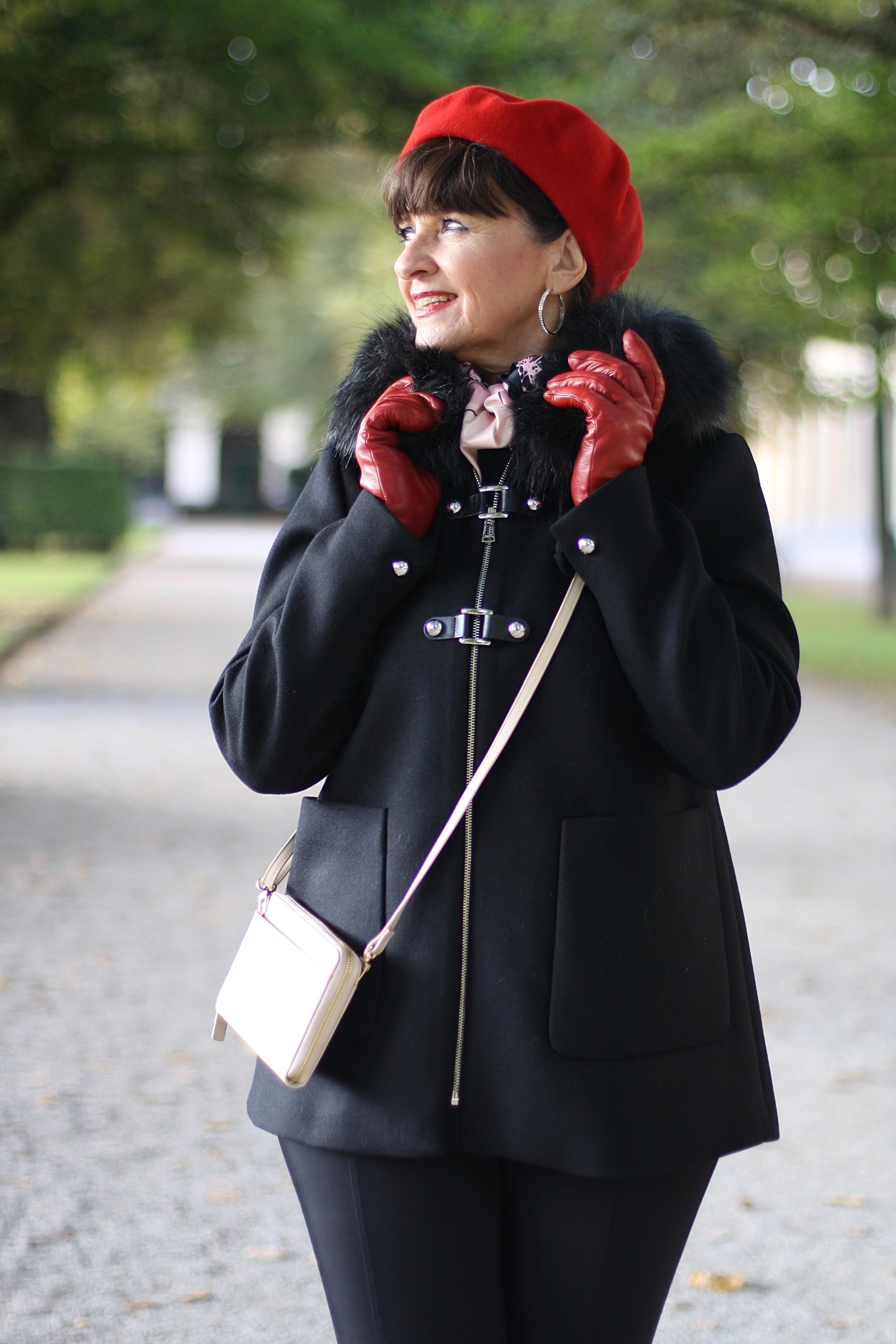 schwarze-jacke-und-rote-muetze-mit-tasche