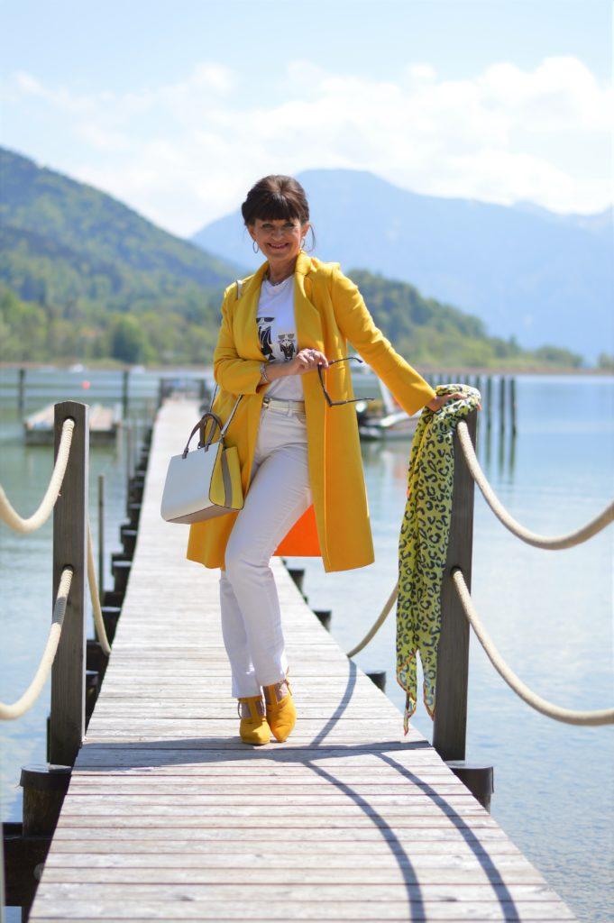 Gelber Mantel kombiniert mit weißer Hose
